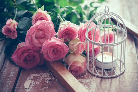 Foto per Bouquet of pink roses, wooden frame and a burning candle in a white decorative bird cage on old board background, vintage decor and color tinting - Immagine Royalty Free