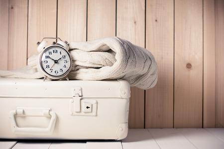Photo pour Beige knitted sweater, alarm clock and vintage suitcase on wooden background, retro decor - image libre de droit