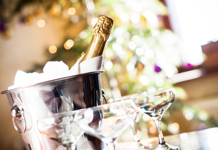 Photo for Luxury holiday composition, a bottle of chilled champagne in an ice bucket and vintage glasses, festive lights in the background - Royalty Free Image