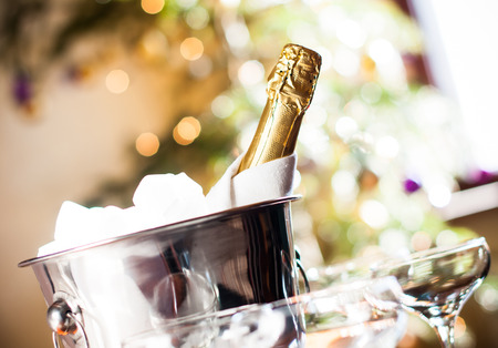 Photo pour Luxurious holiday composition, a bottle of chilled champagne in an ice bucket and napkin closeup on lights background - image libre de droit