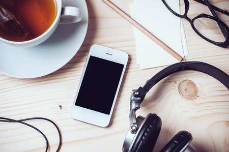 Foto de Paper records, cup of tea, mobile phone, headphones, glasses and pencil on wooden office desktop, hipster style - Imagen libre de derechos