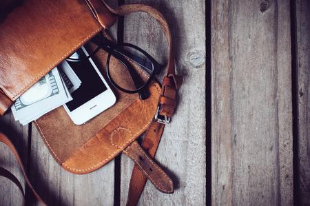 Foto de Optical glasses, money and smartphone in an open leather hipster's bag on a wooden board background. - Imagen libre de derechos