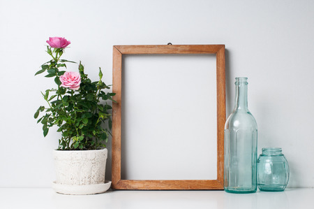 Foto de Vintage blank wooden frame, bottles and rose in a pot on a white wall - Imagen libre de derechos