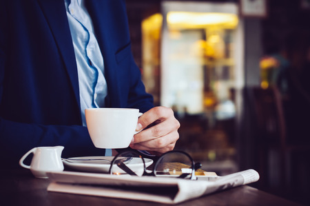 Photo pour Businessman in a blue jacket with a cup of coffee, reading glasses, newspaper and smartphone in a cafe at the table, close-up - image libre de droit