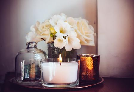 Foto de Bouquet of white flowers in a vase, candles on vintage copper tray, wedding home decor on a table - Imagen libre de derechos