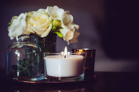 Photo pour Bouquet of flowers in a vase, candles on a tray, vintage home decor on an a table, dark tones - image libre de droit