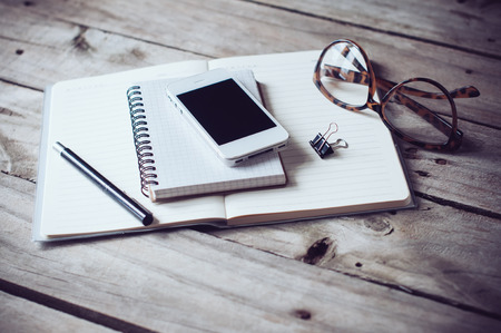 Foto de Hipster home office tabletop: papers and notebooks, reading glasses, smart phone, pen on an old wooden board background - Imagen libre de derechos