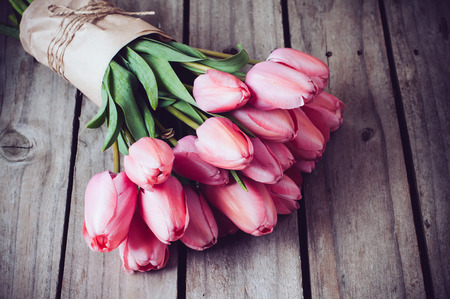 Photo pour Bunch of fresh spring pink tulips on old vintage wooden board, copy space - image libre de droit
