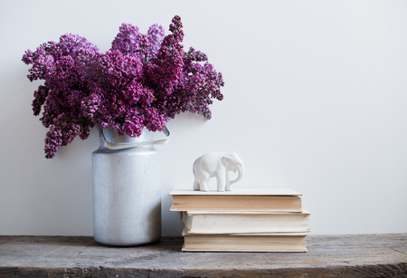 Photo for Home interior decor, bouquet of lilacs in a vase and books on rustic wooden table, on a white wall background - Royalty Free Image