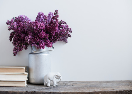 Photo pour Home interior decor, bouquet of lilacs in a vase and books on rustic wooden table, on a white wall background - image libre de droit