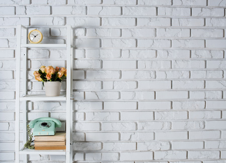 Photo pour Shelf with interior decoration in front of a white brick wall, vintage decor - image libre de droit