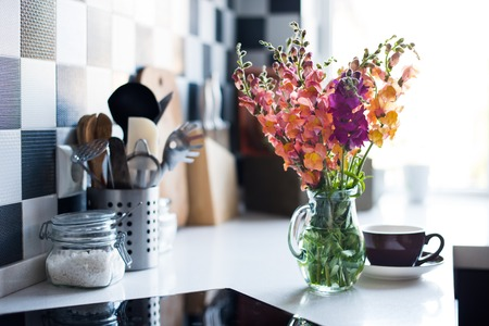 Foto de Bunch of fresh summer flowers in a jug in home interior of modern kitchen, close-up - Imagen libre de derechos