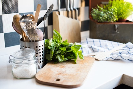 Photo for A bunch of basil on the board on the kitchen table, home kitchen supplies for cooking. - Royalty Free Image