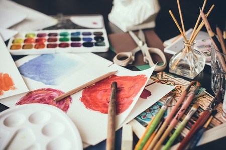 Photo for Mess in the the artist's studio, watercolor paints, brushes and sketches, palette and painting tools. Designer's working place, hipster style. - Royalty Free Image