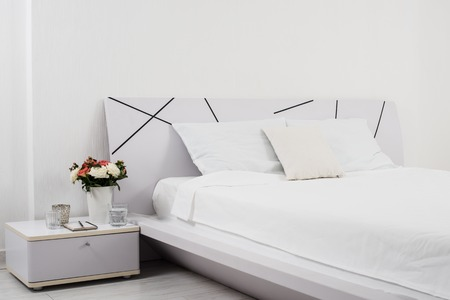 Foto de Interior of white bedroom, new linens on the bed in the hotel room - Imagen libre de derechos
