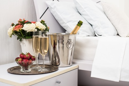 Photo for Champagne in bed in a hotel room, ice bucket, glasses and fruits on white linen - Royalty Free Image