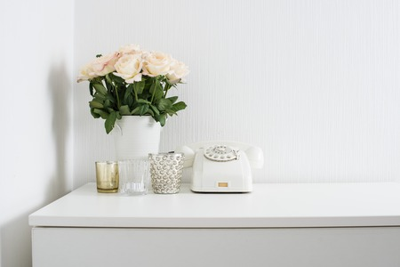 Photo pour Modern interior decor with vintage details: white rotary phone and fresh flowers on a table. Clean white room in real apartment. - image libre de droit