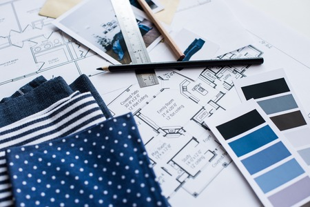 Interior designer's working table, an architectural plan of the house, a color palette, furniture and fabric samples in blue color. Drawings and plans for house decoration.