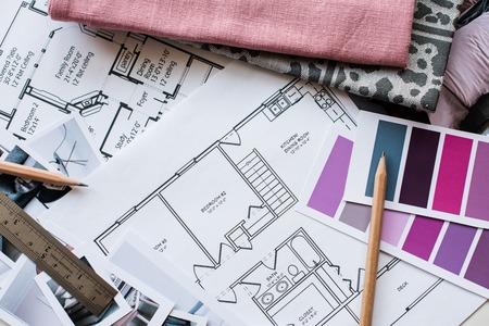 Photo pour Interior designer's working table, an architectural plan of the house, a color palette, furniture and fabric samples in grey and pink color. Drawings and plans for house decoration. - image libre de droit