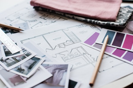 Foto de Interior designer's working table, an architectural plan of the house, a color palette, furniture and fabric samples in grey and pink color. Drawings and plans for house decoration. - Imagen libre de derechos