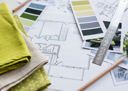 Photo pour Interior designer's working table, an architectural plan of the house, a color palette, furniture and fabric samples in yellow and grey color. Drawings and plans for house decoration. - image libre de droit