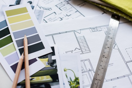 Foto de Interior designer's working table, an architectural plan of the house, a color palette, furniture and fabric samples in yellow and grey color. Drawings and plans for house decoration. - Imagen libre de derechos