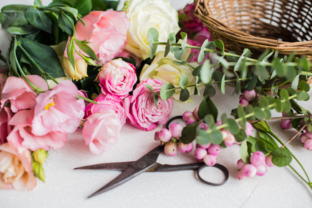 Foto de Fresh flowers, leaves, and tools to create a bouquet on a table, florist's workplace. - Imagen libre de derechos