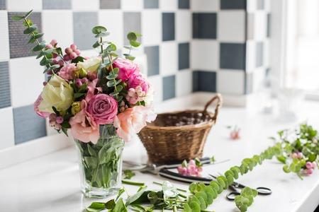 Photo pour Just created bouquet of fresh flowers and leaves, scissors on a table, florist's studio. - image libre de droit