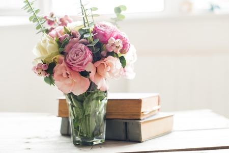 Photo pour Elegant bouquet of pink flowers and ancient books on a tabke with backlight. Vintage decor. - image libre de droit