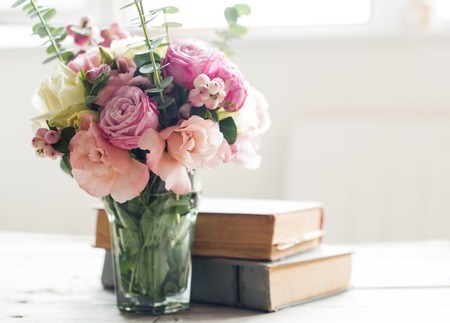 Elegant bouquet of pink flowers and ancient books on a tabke with backlight. Vintage decor.