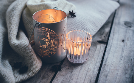 Photo for Cosy and soft winter background, knitted sweater and candles on an old vintage wooden board. Christmas holidays at home. - Royalty Free Image