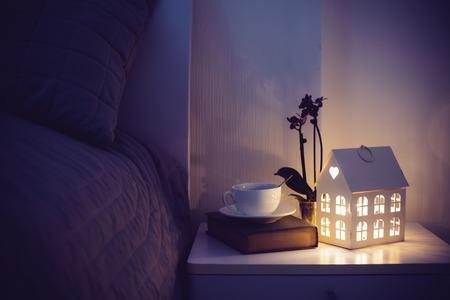 Photo for Cozy evening bedroom interior, cup of tea and a night light on the bedside table. Home interior decor with warm light. - Royalty Free Image