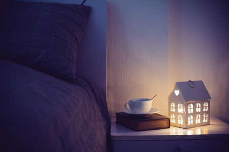 Photo pour Cozy evening bedroom interior, cup of tea and a night light on the bedside table. Home interior decor with warm light. - image libre de droit