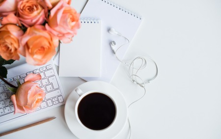 Photo for Bright white office table decor with fresh flowers, computer keyboard and smart phone. Woman's modern workspace, interior details. - Royalty Free Image