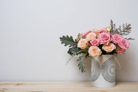 Foto de Bouquet of pink and beige roses in a decorative vase on a shelf in home interior, simple home decor - Imagen libre de derechos