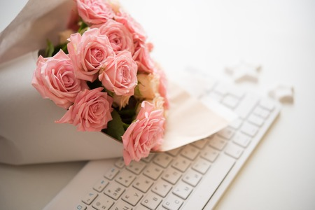 Photo pour Bouquet of pink and beige roses on white computer keyboard, modern workplace closeup - image libre de droit