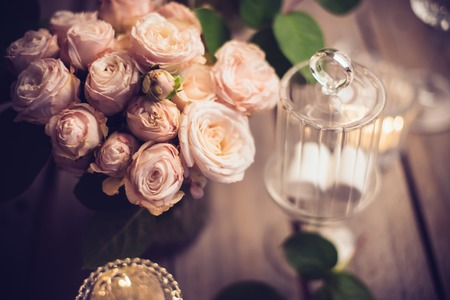 Foto de Elegant vintage wedding table decoration with roses and candles, warm night light filter - Imagen libre de derechos