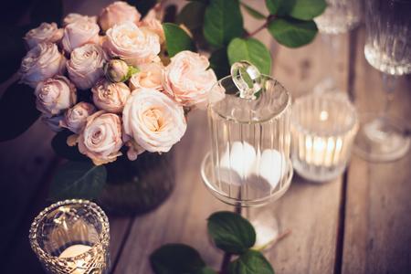 Foto de Elegant vintage wedding table decoration with roses and candles, warm night light filter - Imagen libre de derechos
