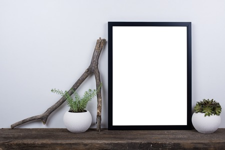 Foto de Scandinavian style empty photo poster frame mock up. Minimal home decor on rustic wooden board with white wall background. - Imagen libre de derechos