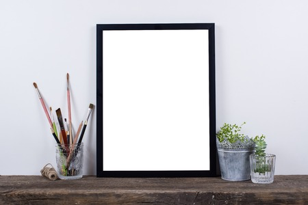 Photo pour Scandinavian style empty photo poster frame mock up. Minimal home decor on rustic wooden board with white wall background. - image libre de droit