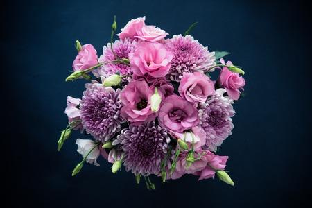 Photo pour Bouquet of pink flowers closeup on black background, eustoma and chrysanthemum, elegant vintage floral decor, top view - image libre de droit