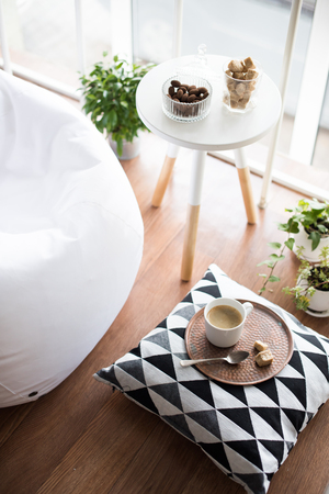 Photo pour Coffee served on table in bright light scandinavian style hipster interior, cozy loft room with large windows closeup - image libre de droit