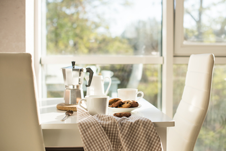 Foto de Early morning french home breakfast, coffee and cookies on the table near window in bright sunlight, white interior - Imagen libre de derechos