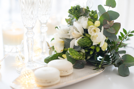 Photo for Beautiful wedding decoration with champagne and white flowers, elegant decor with crystal wine glasses and macaron sweets - Royalty Free Image