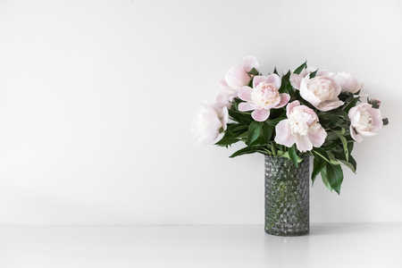 Photo for Bouquet of tender pink peonies in vase near white wall - Royalty Free Image