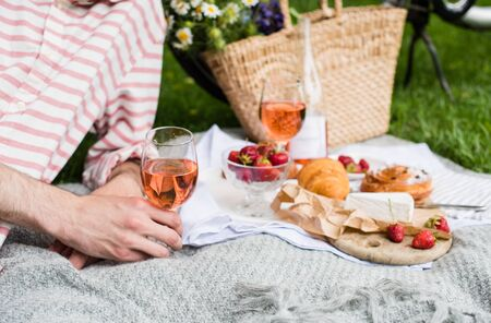 Photo pour Mans hand holding glass of rose wine, summer picnic with cheese and wine - image libre de droit