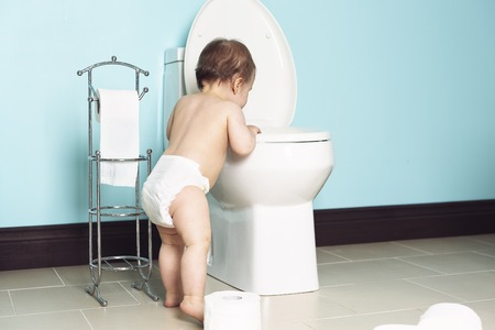 A Toddler in bathroom look at the toilet