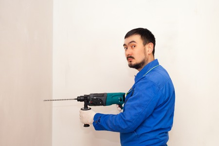 Photo for Drill in hands. working the wall drill impact drill, hammer - Royalty Free Image