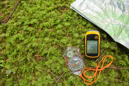 Foto de finding the right position in the forest with a compass, map  and GPS - Imagen libre de derechos