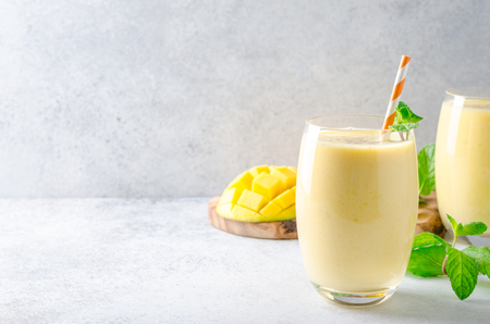 Foto de Mango lassi with mint leaves, traditional indian drink in glasses on a light gray stone table. Front view, horizontal image, copy space - Imagen libre de derechos